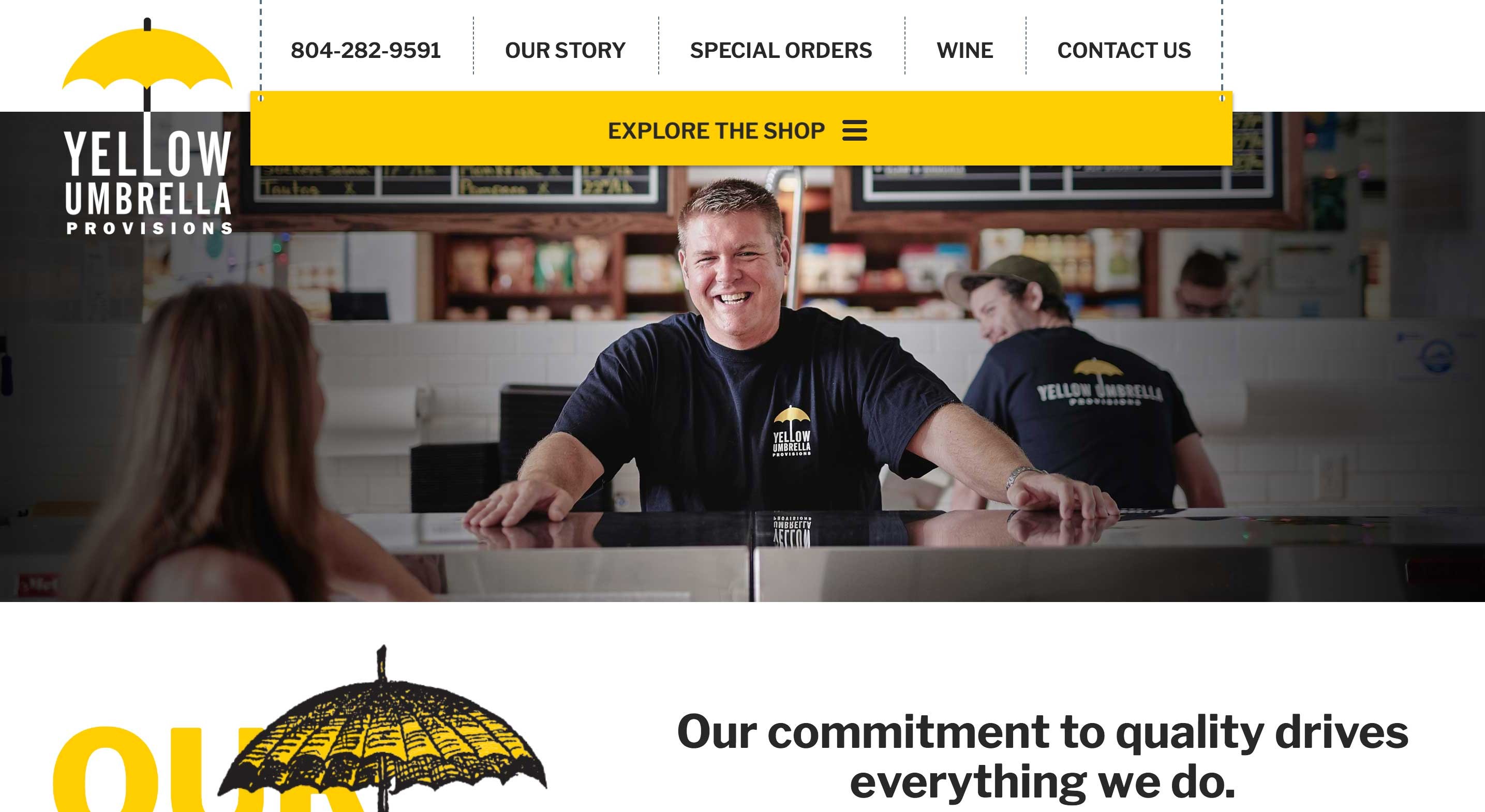 A man standing behind the counter of the Yellow Umbrella shop smiles as a customer approaches
